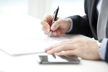 Close-up of businessman sitting at office and signing contract