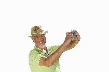 senior man in straw hat taking a photograph, cut out