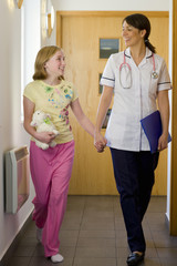 Nurse and girl holding hands and walking down corridor