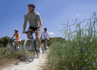 Men and woman riding bicycles on rural path