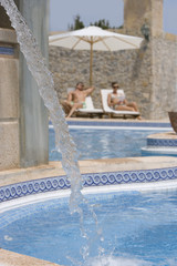 Couple relaxing in lounge chairs at poolside with fountain in foreground