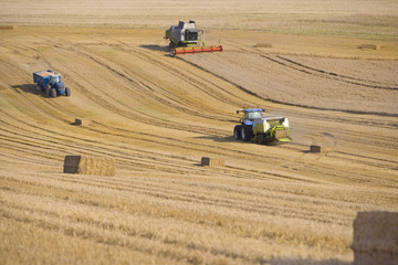 Tractors, straw balers and combine in sunny, rural field