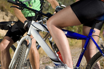 Midsection of couple on mountain bikes stopping for break