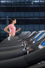 Woman running on treadmill in health club