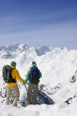 Couple with backpacks holding hands on snowy mountain