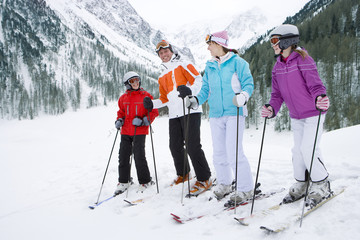 Family standing on skis in remote valley