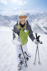 Smiling skier standing with skis and poles on mountain top