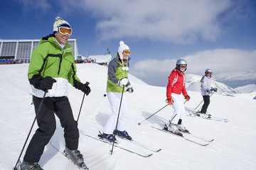 Family of skiers skiing downhill on ski slope