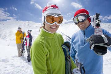 Smiling friends carrying skis
