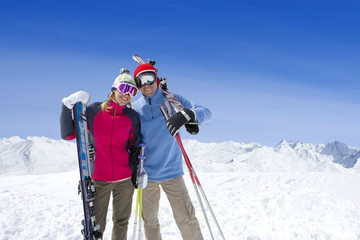 Couple holding skis standing on mountain top together