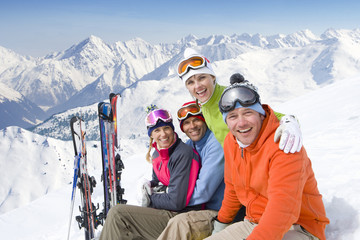 Smiling friends sitting with skis in snow