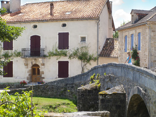 Tourist standing on cobblestone bridge in St Jean de Cole, Dordogne, France