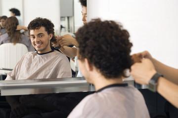 Hairdresser cutting man's hair in salon, reflection in mirror, smiling, rear view, portrait