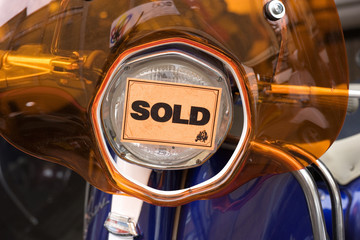 Orange sold sticker on scooter headlight in shop, close-up, front view