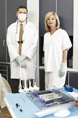Male dentist in surgical mask standing beside assistant in dental surgery, portrait