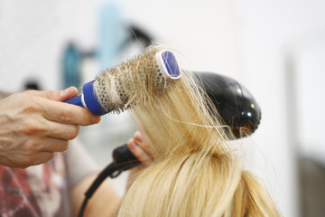 Blonde woman drying hair at salon