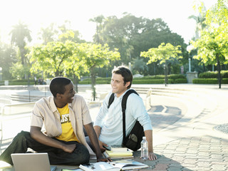 Two male university students sitting on ground with textbooks and laptop, smiling