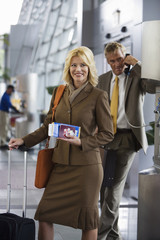 Businessman using pay phone in airport terminal, focus on businesswoman with luggage and ticket, portrait