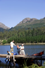 Boy (8-10) sitting on lake jetty, father and grandfather loading motorboat with provisions
