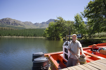 Senior man standing in motorboat beside lake jetty, tying rope to mooring post, smiling, portrait