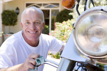 Senior man polishing motorbike on driveway, crouching down, smiling, close-up, portrait