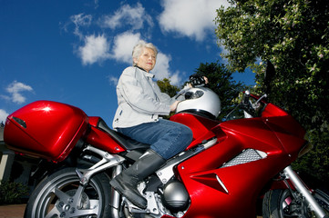 Senior woman sitting on red motorbike on driveway, holding crash helmet, side view, portrait, low angle view