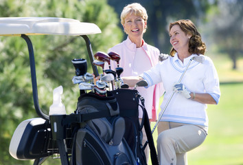 Two mature women standing beside parked golf buggy, playing golf, brunette holding golf club, smiling, portrait