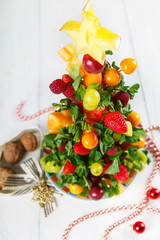 Creative fruit Christmas tree with different berries, fruits and
