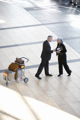 Senior businessman and woman shaking hands near luggage trolley in airport, side view, elevated view