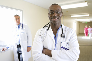 Young male doctor standing in hospital corridor, smiling, mature male doctor in background, portrait