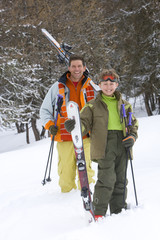 Father and son (7-9) standing in snow by skis, smiling, portrait