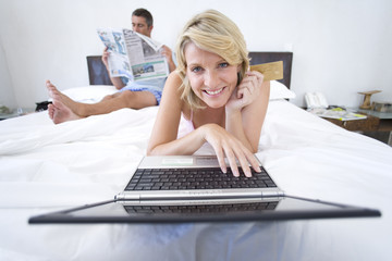 Woman using laptop on bed, smiling, portrait, man reading newspaper in background