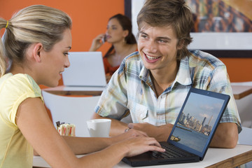 Young man smiling by young woman using laptop in cafe, young woman with laptop in background
