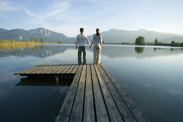 A couple standing at the end of a pier.