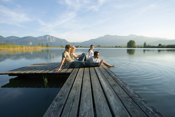 Two couples relaxing on a pier.