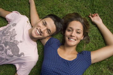 A teenage couple lying down on the grass.