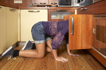 Side profile of a woman looking into a cabinet in the kitchen