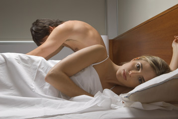 Couple ignoring each other in bed