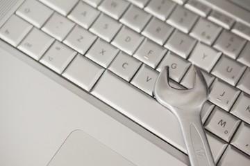 Pliers lying on silver keyboard
