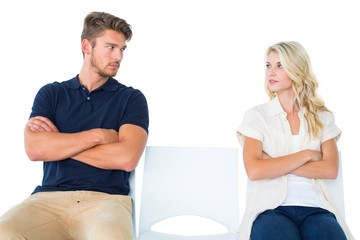 Young couple sitting in chairs not talking during argument