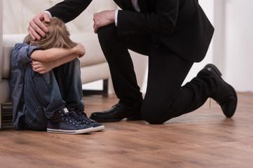 Father kneeling and comforts sad child.