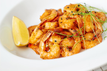 Prawns on white plate with garlic chives and lemon