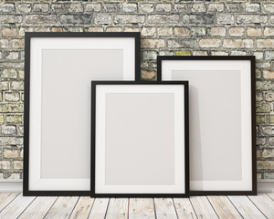 three blank black picture frames on the old brick wall