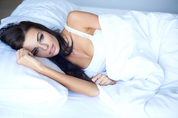 Young woman lying awake in bed thinking