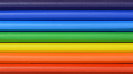 Close up of rainbow colored wax crayons in rows