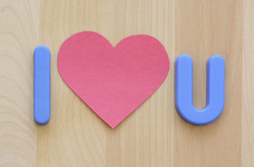 Close up of I love U in plastic toy letters and pink flat heart