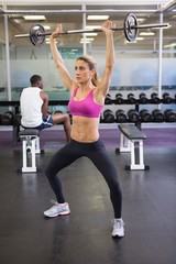 Full length of fit woman lifting barbell in gym