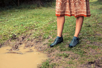 Young woman standing by a puddle in the forest