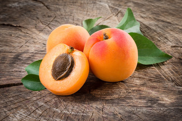 Organic apricots with leaves on wooden background