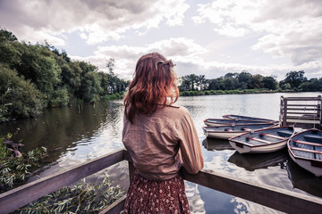 Young woman looking at boats in lake
